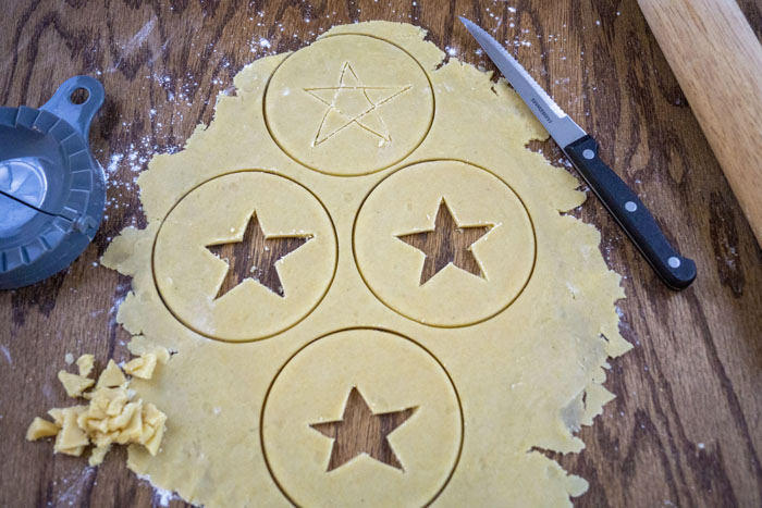 Dough rolled out on wooden surface with circles and stars cut out