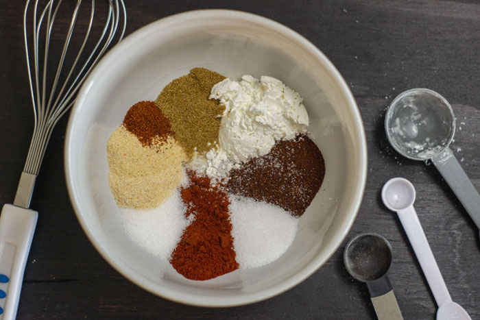 Fajita seasonings placed in a white bowl before mixing with a wire whisk and measuring spoons