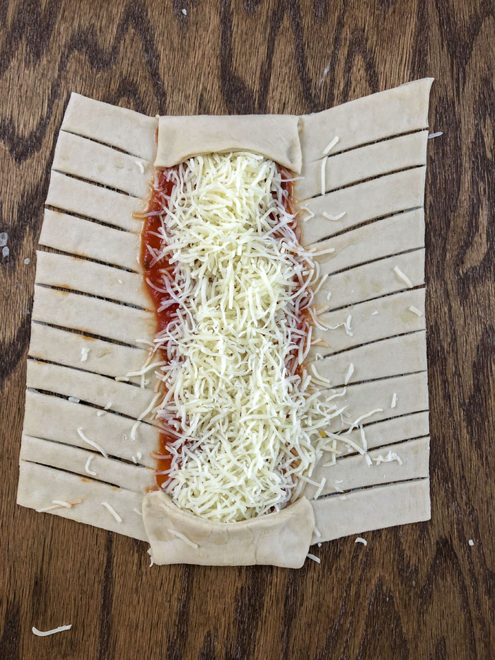 Dough with diagonal cuts on a wooden background with pizza toppings down the center