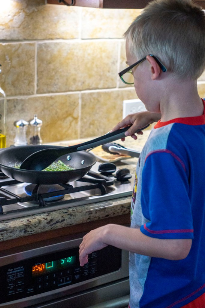 Young boy standing in front of stove using a mixing spoon to prepare roasted asparagus