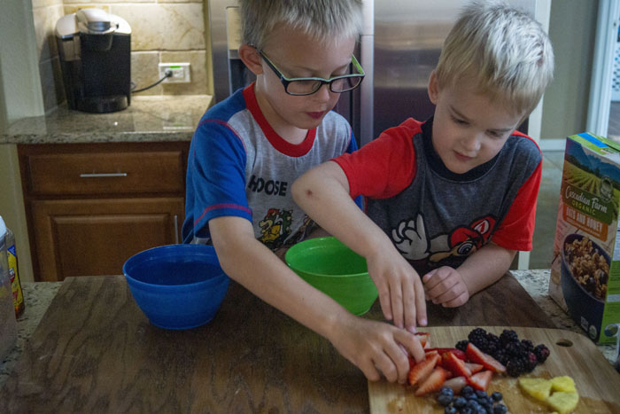 Two young boys building yogurt bowls