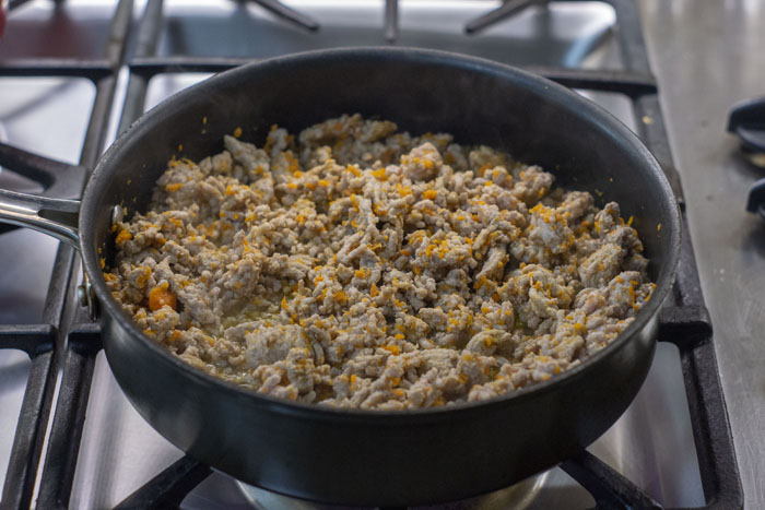 Large skillet with browned ground pork and diced carrots cooking over a gas stovetop