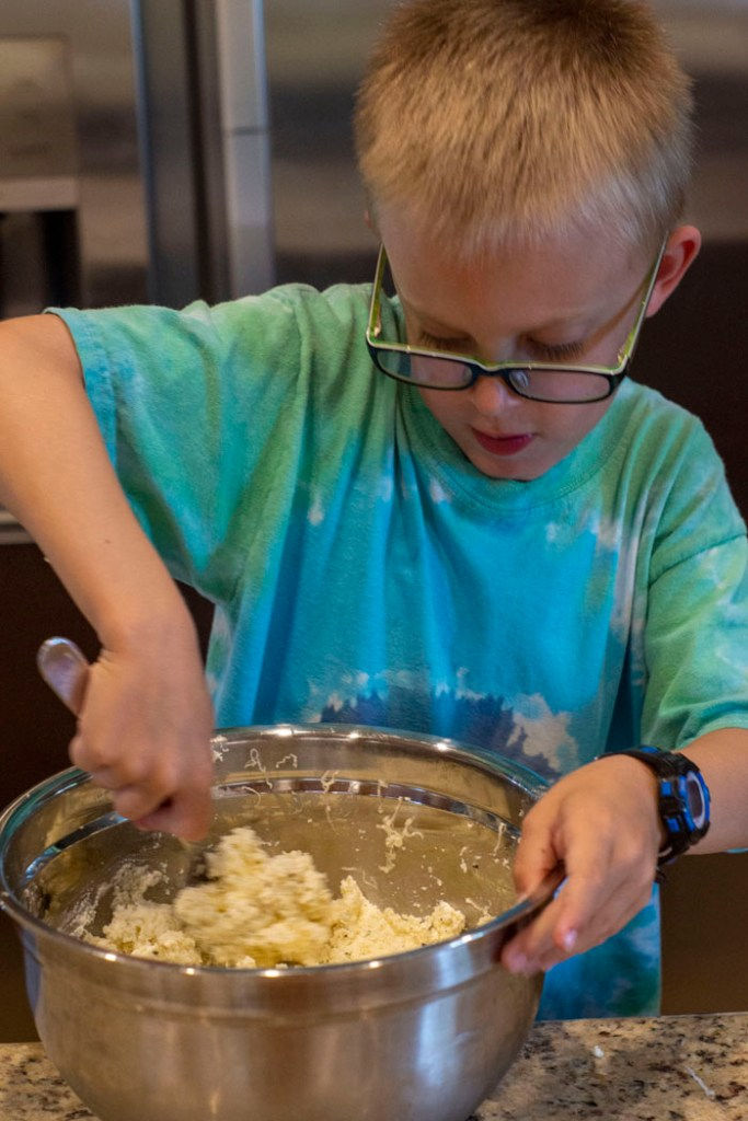 Young boy stirring cheeses together in a stainless steel mixing bowl