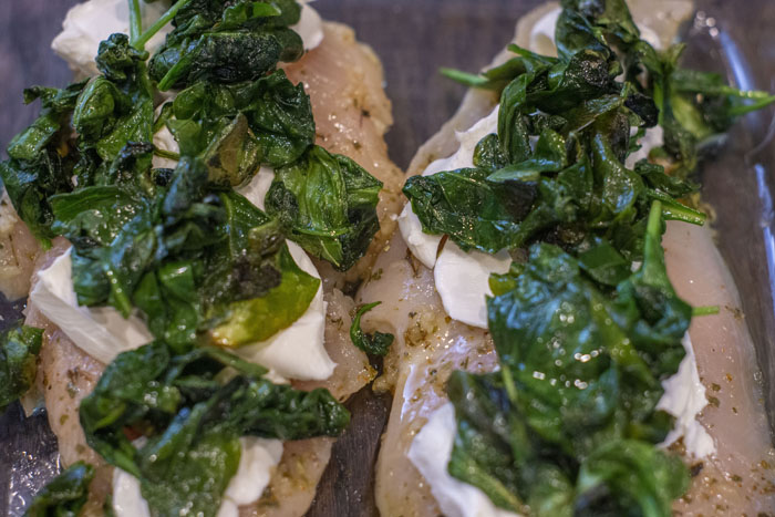 Close up of raw chicken covered with cream cheese and wilted spinach leaves on a wooden surface