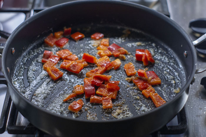 Large skillet over a gas stovetop with chopped red bell peppers