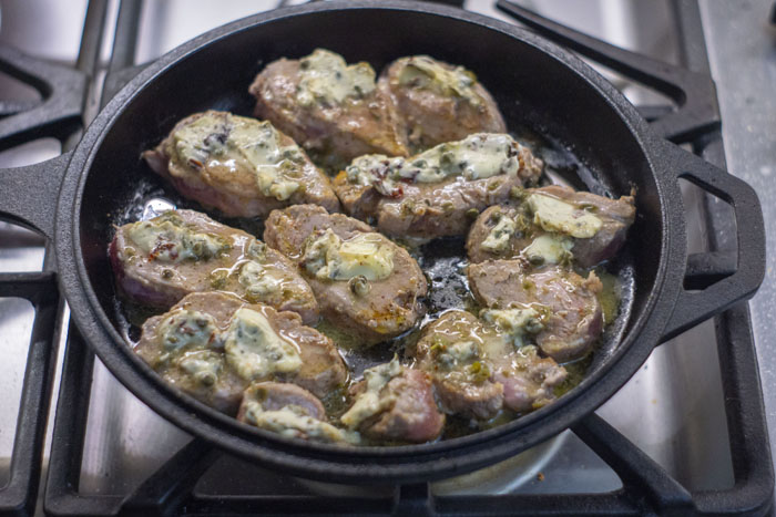 Cast iron skillet with sliced pork covered in tomato-caper butter cooking over a gas stovetop