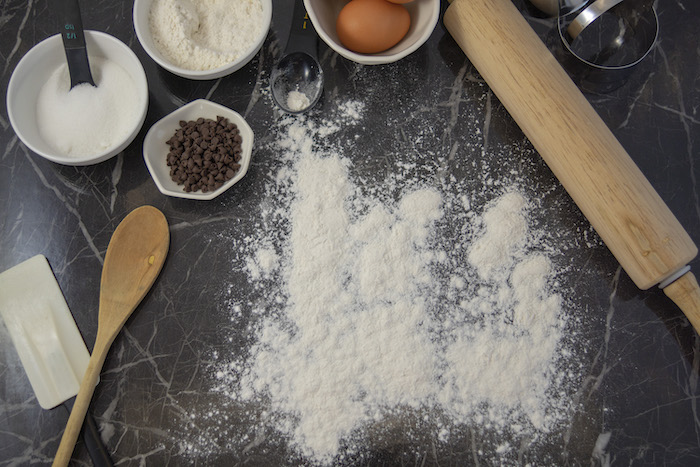 Pile of flour surrounded by an assortment of baking equipment and ingredients on a black marble surface