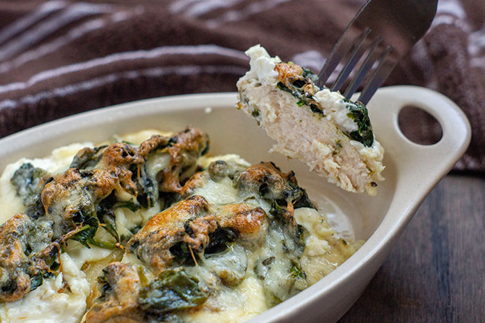 Chicken and Spinach Casserole with Cream Cheese in a tan bowl on a wooden surface with a piece of chicken held up on a fork