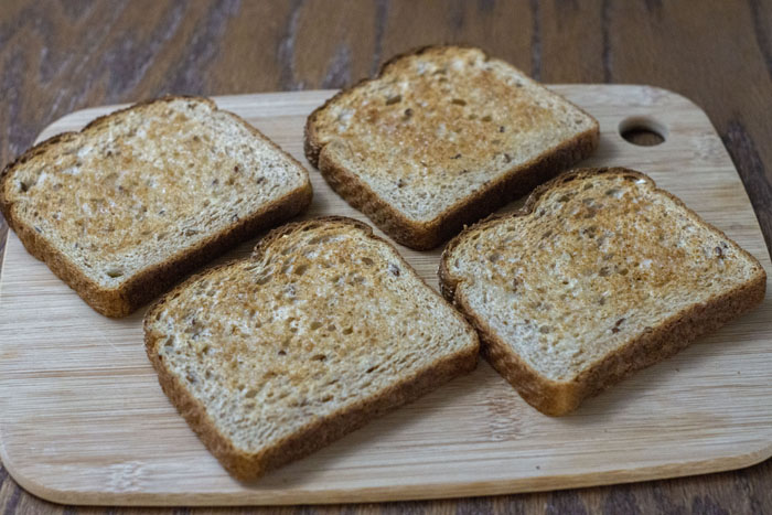 4 slices of toasted bread on a bamboo cutting board on a wooden surface