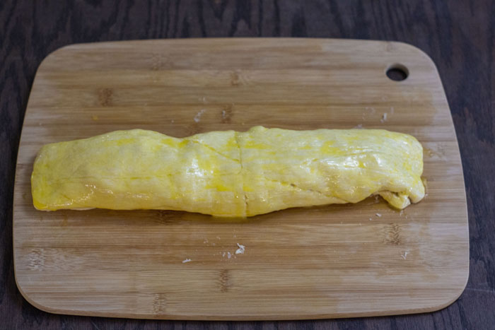 Rolled up crescent roll dough covered with an egg wash on a bamboo cutting board on a wooden surface