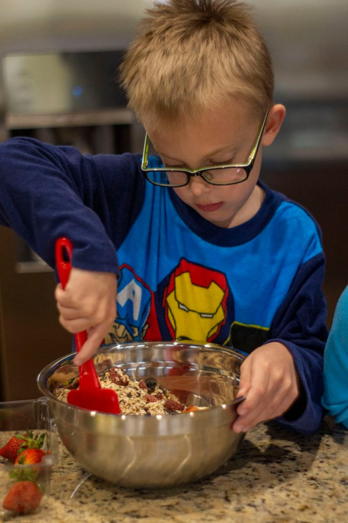 Young boy mixing ingredients with a red spatula in a stainless steel mixing bowl
