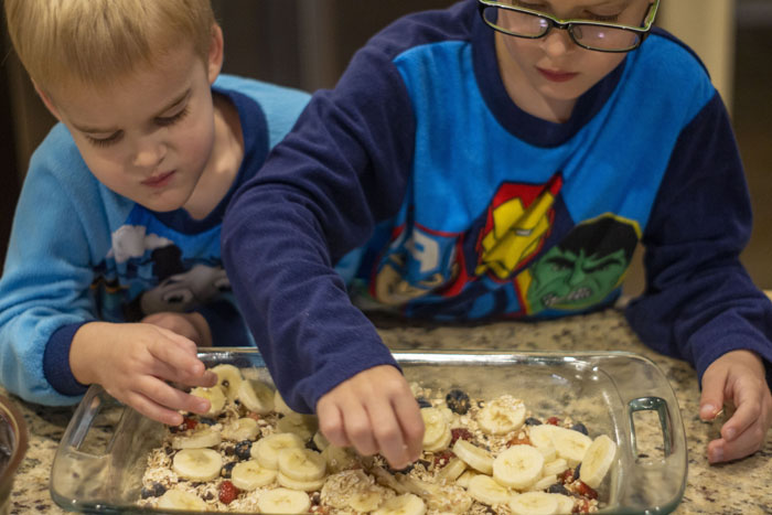 Two young boys placing bananas in a layer on oatmeal breakfast bars in a glass baking dish