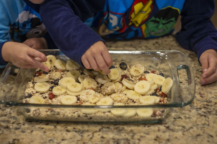 Two small hands adding a layer to oatmeal breakfast bars