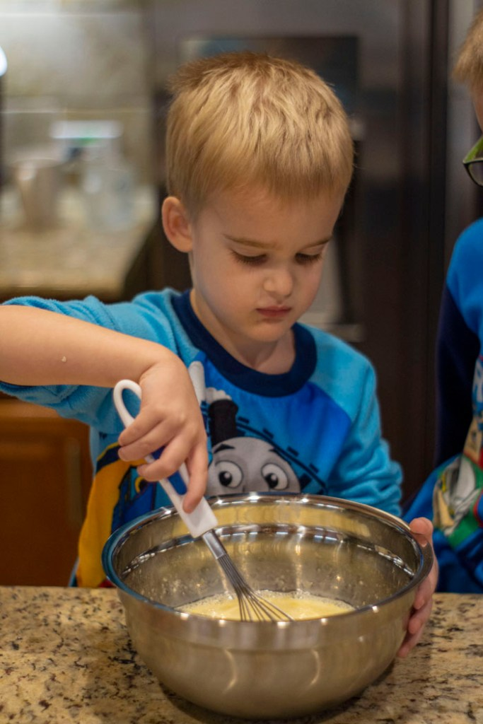 Young boy whisking ingredients in a stainless steel mixing bowl