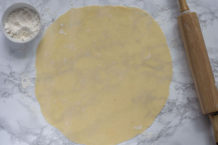 Pie crust rolled out on a marble surface next to a white bowl of flour and a wooden rolling pin