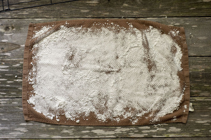 Overhead of a brown dish towel sprinkled with powdered sugar on a wooden surface