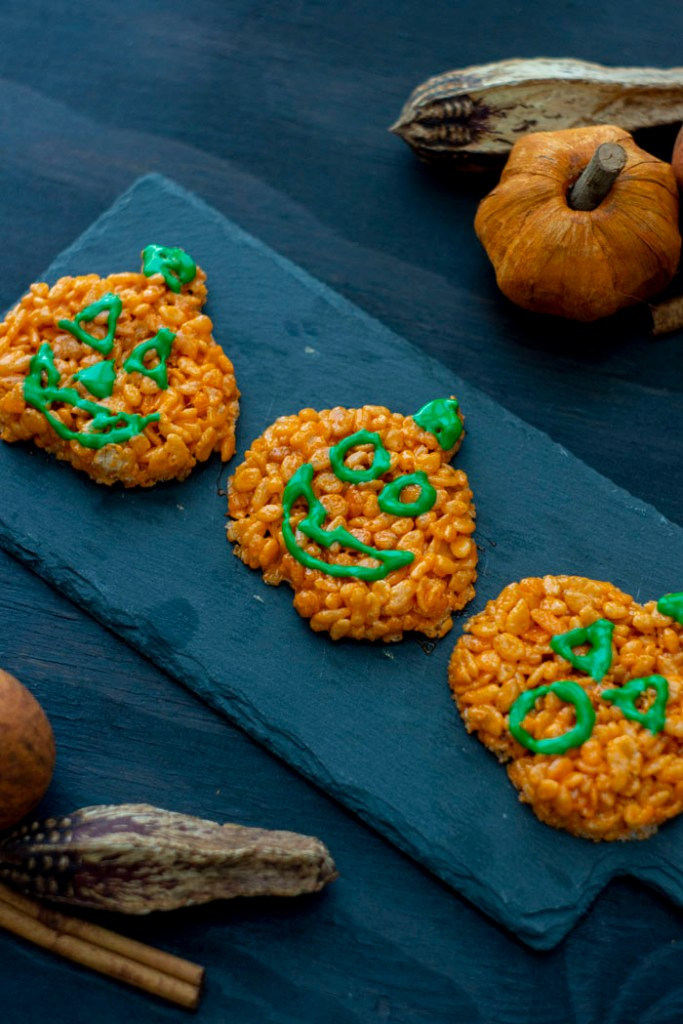 Pumpkin-shaped rice krispies with faces in green icing on a slate serving board on a dark wooden surface with fall decorations (vertical)