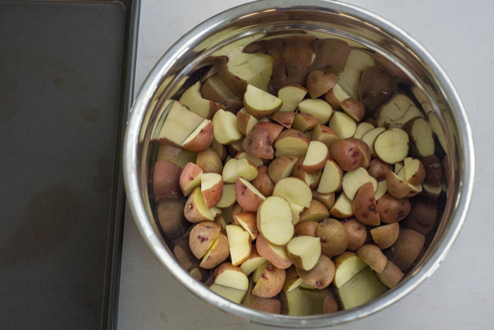 Cut red potatoes in a stainless steel mixing bowl next to a metal baking sheet on a white surface