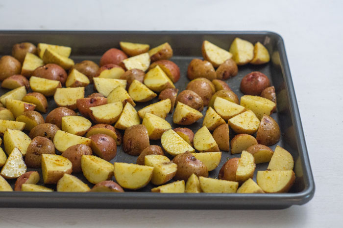 Cut potatoes covered with oil and seasonings spread out in a single layer on a metal baking sheet on a white surface