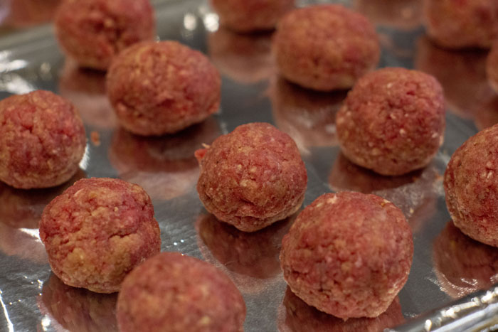 Close up of formed meatballs on aluminum foil