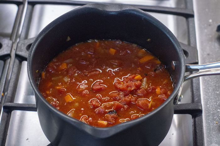 Canned diced tomatoes mixed into a medium saucepan with tomato paste and diced vegetables all on a gas stovetop