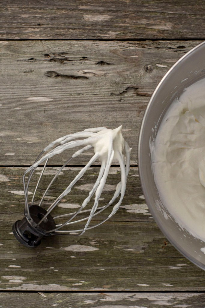 Wire whisk from stand mixer covered with homemade whipped topping next to a stainless steel bowl of whipped topping on a wooden surface (vertical)