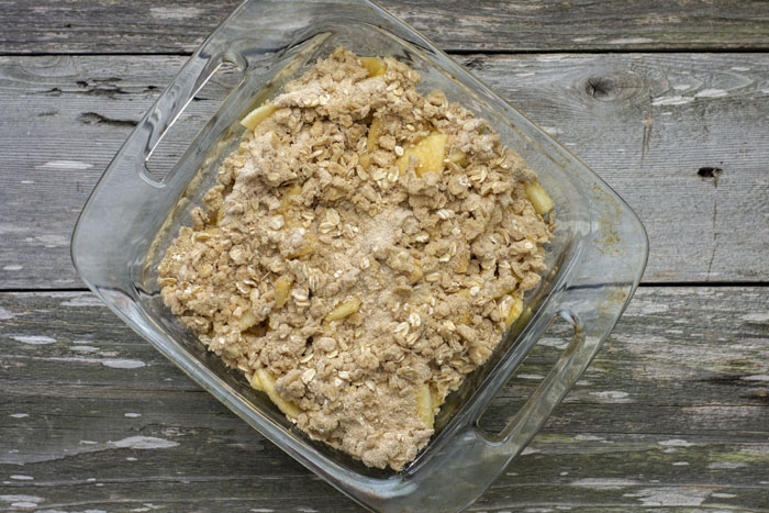 Glass baking dish filled with sliced apples topped with crisp crumble all on a wooden surface