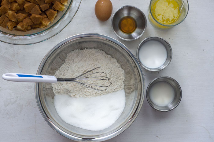 Large stainless steel mixing bowl with dry ingredients and a wire whisk sitting next to a few other stainless steel bowls with liquid ingredients, a cup of melted butter, an egg, and a pie pan full of apple chunks covered in cinnamon on a white surface