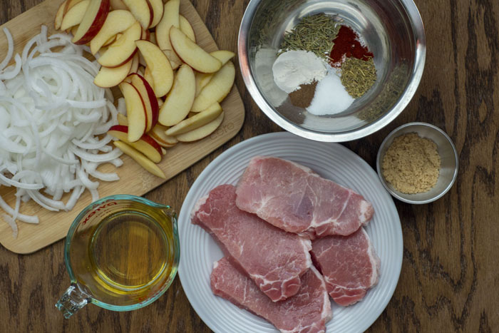 White plate with raw pork chops next to a stainless steel bowl of brown sugar, another stainless steel bowl of herbs, a measuring cup with apple juice, and a bamboo cutting board with sliced apples and onions all on a wooden surface