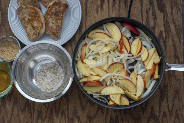 Skillet with cooked sliced onions and apples next to a stainless steel bowl of an herb mixture and another stainless steel bowl with brown sugar, a glass measuring cup with apple sauce, and plate of cooked pork chops all on a wooden surface