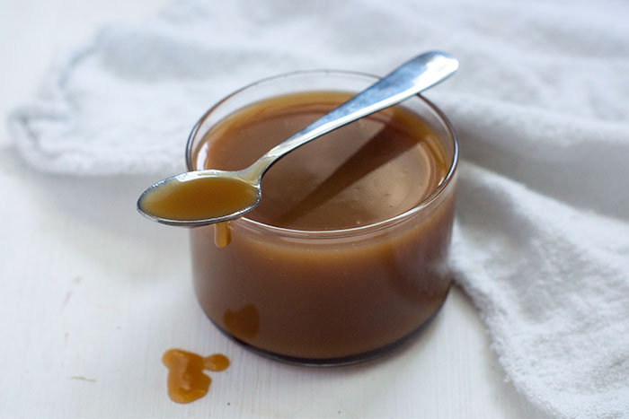 Butterscotch syrup in a small glass with a stainless steel spoon across the top and syrup dripping from it down the side next to a white towel all on a white surface