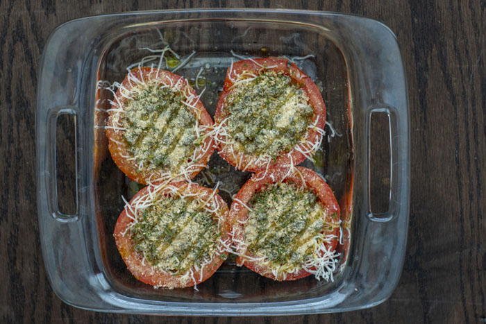 Glass baking dish with tomatoes filled with cheese and herb-caper mixture drizzled with olive oil all on a wooden surface