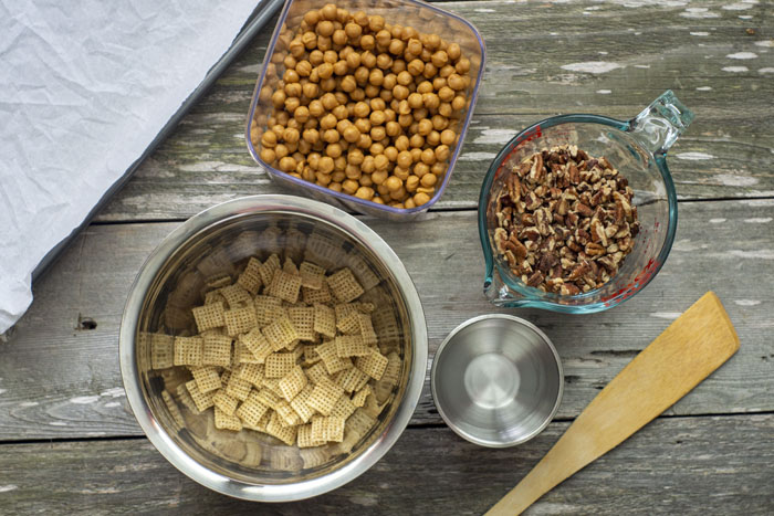 Stainless steel bowl of rice squares cereal next to a small stainless steel bowl with water, a glass measuring cup of chopped pecans, a plastic dish of caramels, a sheet pan covered with parchment paper, and a wooden spatula all on a wooden surface