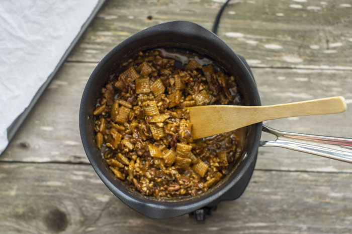 Saucepan with melted caramels, rice squares, and chopped pecans and a wooden spoon inside sitting next to a baking sheet covered with parchment paper all on a wooden surface