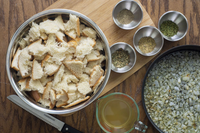 Large stainless steel bowl of chopped bread next to stainless steel bowls of dried herbs on a wooden cutting board next to a glass measuring cup of chicken broth and a bread knife beside a frying pan with cooked onions all on a wooden surface