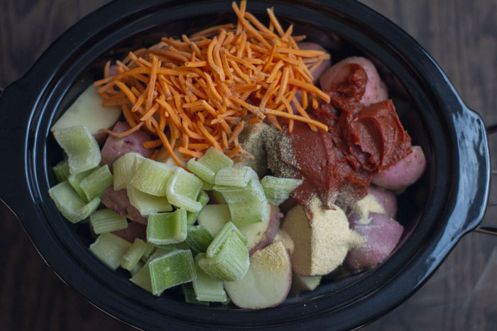 Diced potatoes topped with shredded carrots, diced celery, tomato paste, and seasonings in a slow cooker on a wooden surface