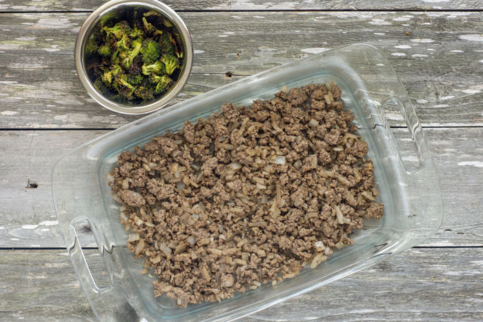 Glass baking dish with cooked ground beef next to a stainless steel bowl of roasted broccoli on a wooden surface