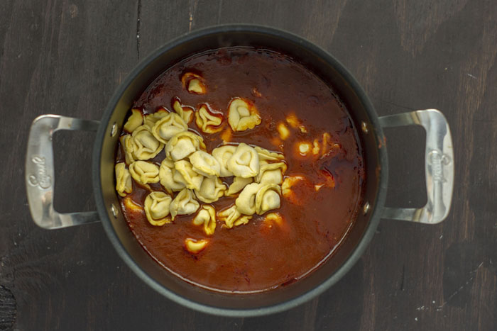 Large stockpot with soup and uncooked tortellini on a wooden surface