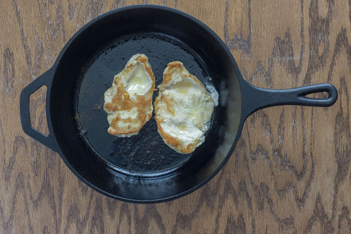 Cast-iron pan with cooked chicken breasts sitting on a wooden surface