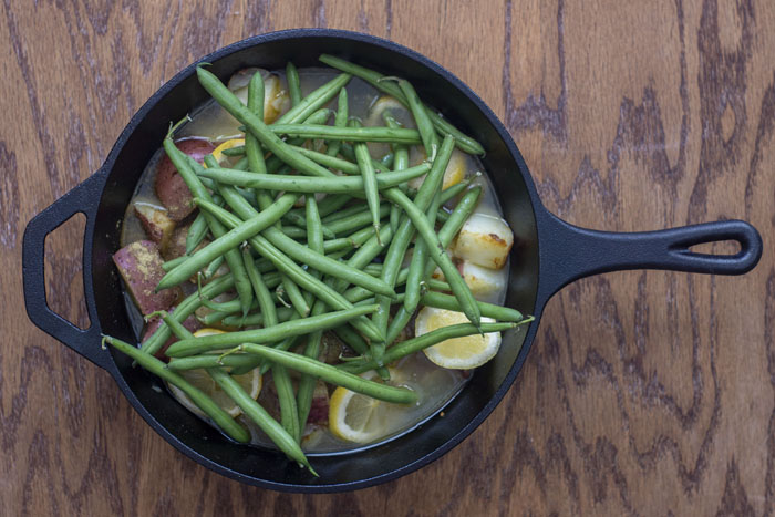 Cast-iron pan with diced tomatoes, lemons, and green beans on a wooden surface