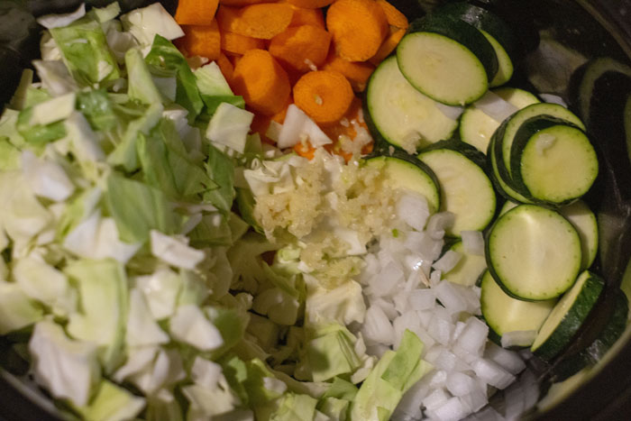 Slow cooker full of chopped and minced vegetables: cabbage, carrots, garlic, onion, zucchini