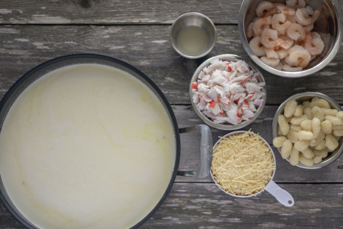 Large skillet with cream and butter next to bowls of ingredients on a wooden surface