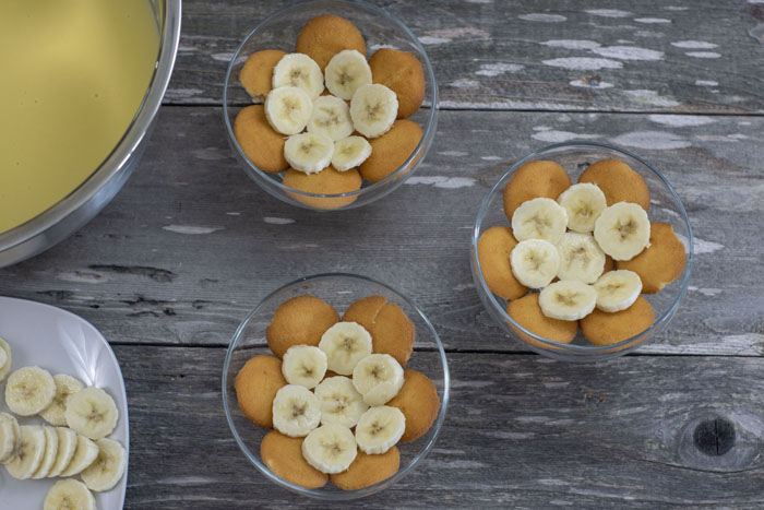 Three individual dessert dishes with a layer of nilla wafers and bananas in each next to a stainless steel bowl with pudding mixture and a plate of sliced bananas all on a wooden surface