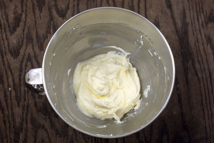 Stainless steel bowl with whisked cream cheese frosting on a wooden surface