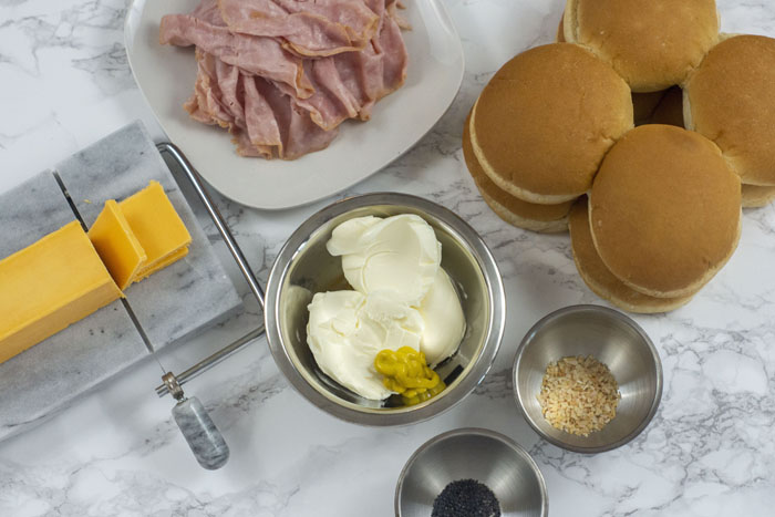 Ingredients ready for Christmas sandwiches: marble cheese slicer with sharp cheddar cheese, white plate with slices of ham, hamburger buns, stainless steel bowl with butter and mustard, minced onion, and poppy seeds all on a white and grey marble surface