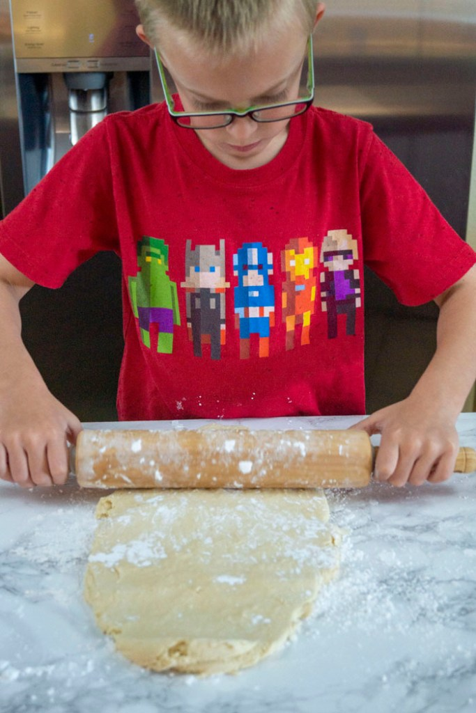 Young boy using a wooden rolling pin to roll cookie dough out on a white and grey marble surface