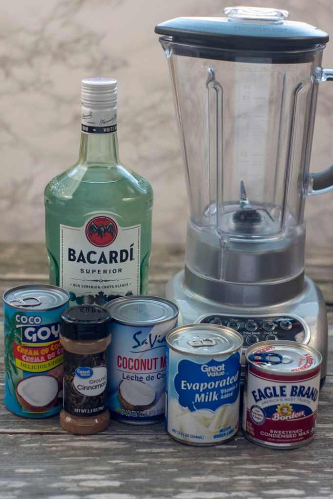 Ingredients ready for coquito: cans of cream of coconut, coconut milk, evaporated milk, and sweetened condensed milk with a bottle of ground cinnamon in front of a glass bottle of rum and a blender all on a wooden surface