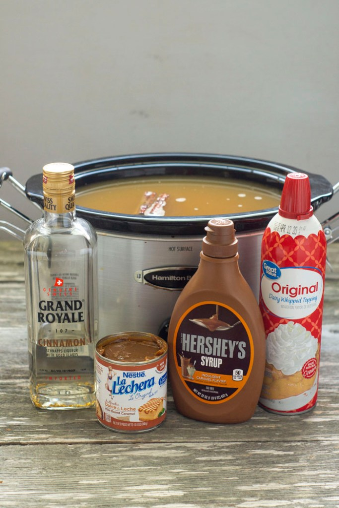 Apple cider with cinnamon sticks in a slow cooker with a bottle of cinnamon schnapps, a can of dulce de leche, a bottle of caramel topping, and a can of whipped topping in front all on a wooden surface