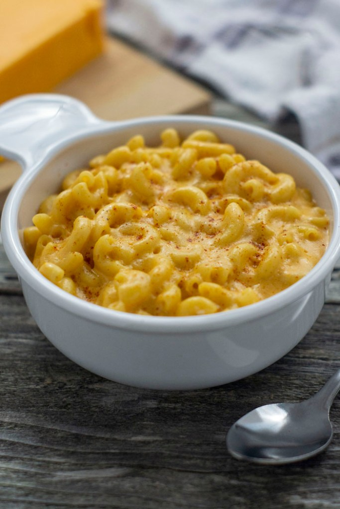 Slow cooker mac and cheese garnished with paprika in a round white bowl next to a spoon with cheddar cheese on a bamboo board behind next to a white and grey towel all on a wooden surface (vertical)