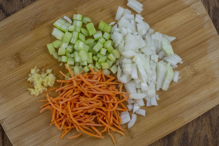 Wooden cutting board with diced celery and onion, shredded carrots, and minced garlic